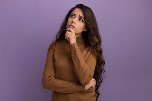 갈색 터틀넥 스웨터를 입고 측면 젊은 아름 다운 소녀를보고 생각 보라색 벽에 고립 된 턱을 잡고