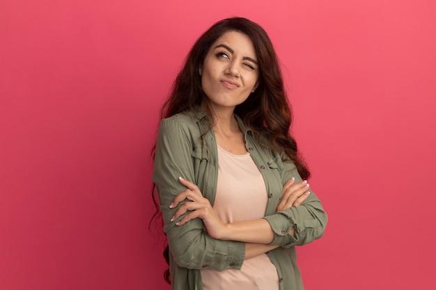 ピンクの壁に分離された手を交差させるオリーブグリーンのtシャツを着ている若い美しい少女の側を見て考え