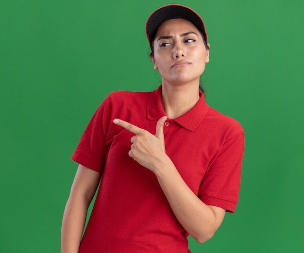 복사 공간 녹색 벽에 고립 된 측면에서 유니폼과 모자 포인트를 입고 측면 젊은 배달 소녀를보고 생각