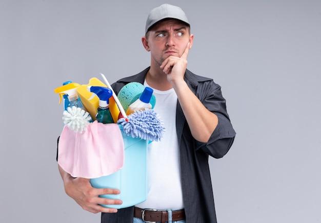 白い壁に隔離された頬に指を置くクリーニングツールのバケツを保持しているtシャツとキャップを身に着けている若いハンサムなクリーニング男を見て考える