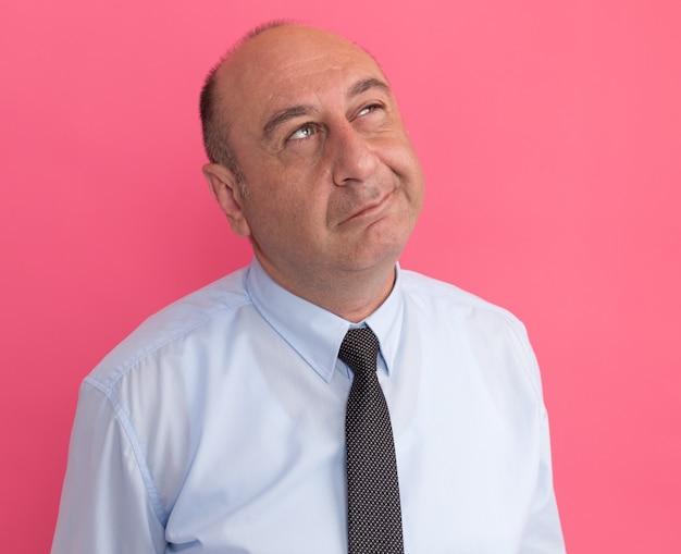 분홍색 벽에 고립 된 넥타이와 흰색 티셔츠를 입고 중년 남자를보고 생각