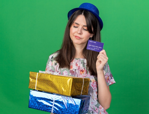 Thinking looking down young beautiful girl wearing party hat holding gift boxes with credit card isolated on green wall