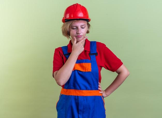 オリーブグリーンの壁に分離された制服をつかんだあごで若いビルダーの女性を見下ろして考えています
