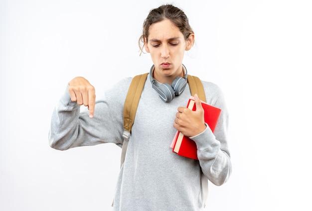 本のポイントを下に保持している首にヘッドフォンでバックパックを身に着けている若い男の学生を見下ろして考える