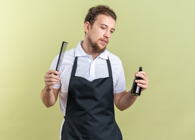 Pensando guardando verso il basso il giovane barbiere maschio che indossa l'uniforme tenendo il flacone spray con pettine isolato su sfondo verde oliva
