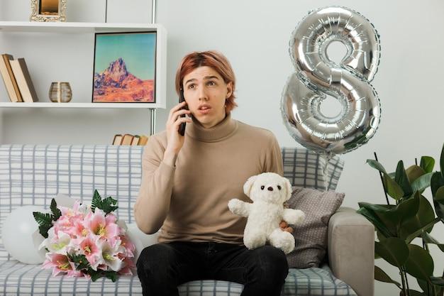 テディベアを持って幸せな女性の日にハンサムな男を見て考えてリビングルームのソファに座って電話で話します