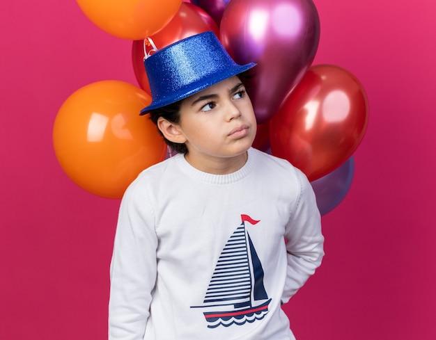 ピンクの壁に分離された前の風船に立っている青いパーティーハットを身に着けている側面を考えて小さな男の子