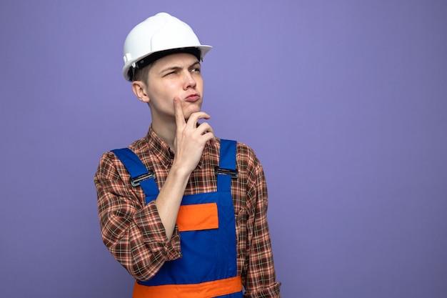 Думая, глядя сторону, положив палец на щеку, молодой мужчина-строитель в униформе