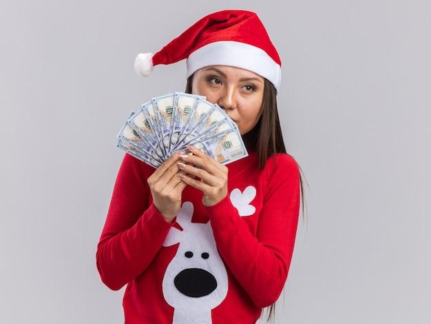 흰색 배경에 고립 된 현금 들고 스웨터와 크리스마스 모자를 쓰고 측면 젊은 아시아 여자를 찾고 생각
