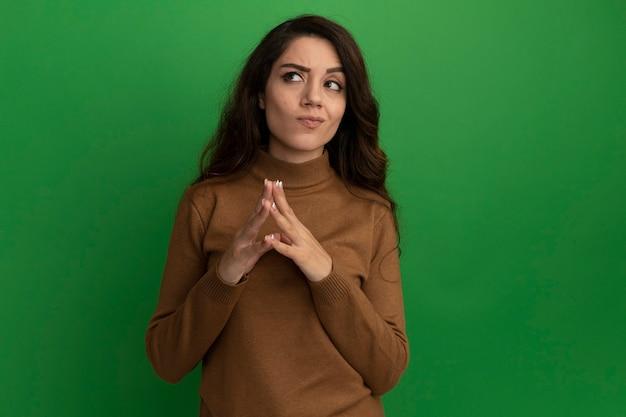Pensando guardando lato giovane bella ragazza mano nella mano insieme isolato sulla parete verde