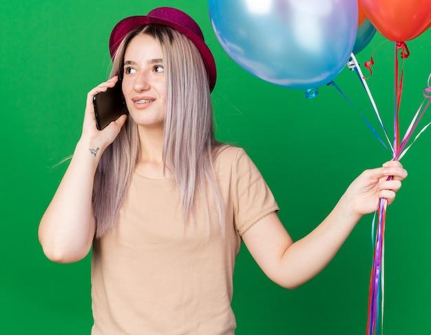 파티 모자를 쓰고 풍선을 들고 있는 중괄호를 쓴 아름다운 소녀가 녹색 벽에 격리된 전화로 말하는 모습을 생각하고 있다