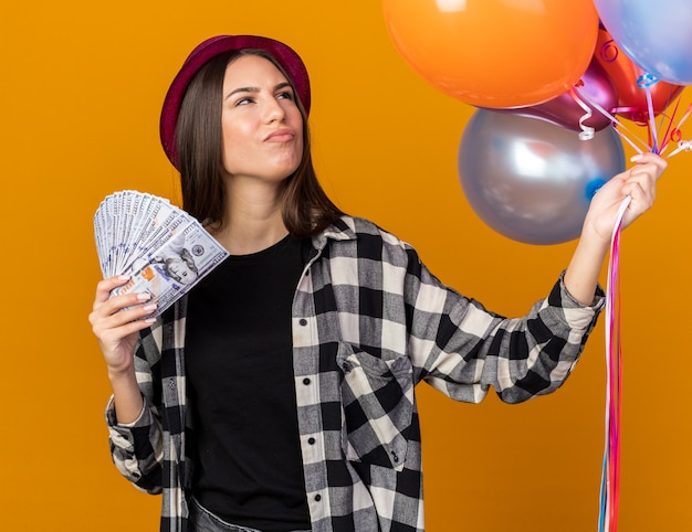 Thinking looking side young beautiful girl wearing party hat holding balloons with cash isolated on orange wall