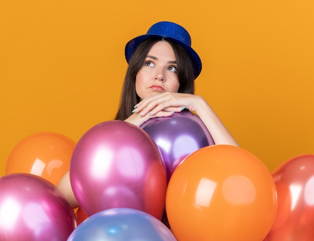 Thinking looking side young beautiful girl wearing party hat standing behind balloons