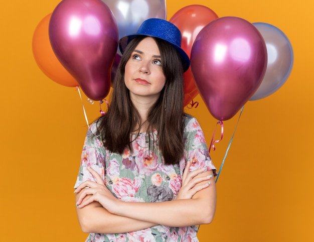 Thinking looking side young beautiful girl wearing party hat standing in front balloons crossing hands
