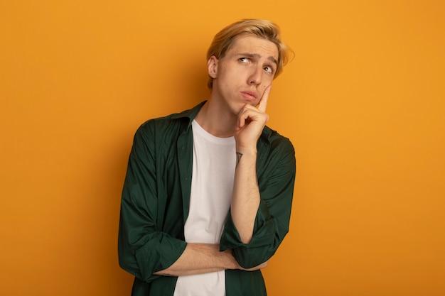 Pensando guardando il giovane ragazzo biondo di lato che indossa la maglietta verde che mette il dito sulla guancia