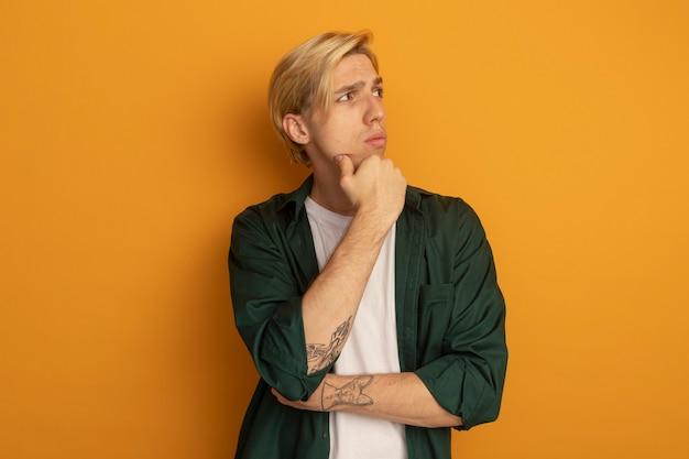 Pensando guardando il giovane ragazzo biondo di lato che indossa la maglietta verde che mette la mano sul mento