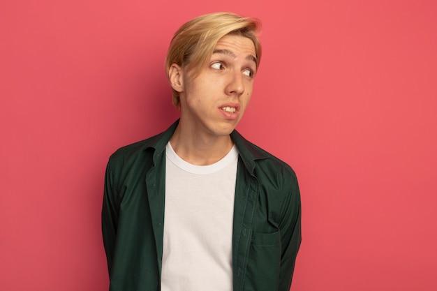 Pensando guardando al lato giovane ragazzo biondo che indossa la maglietta verde