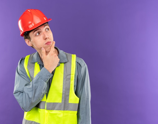 Thinking looking at side young builder man in uniform grabbed chin