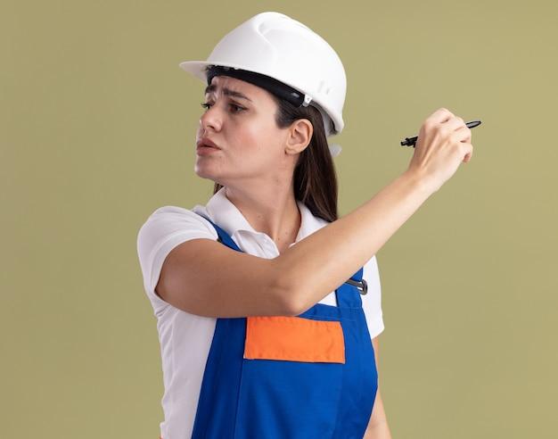 Pensando guardando al lato giovane costruttore donna in uniforme tenendo fuori la penna a lato isolato sulla parete verde oliva