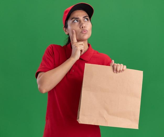 Pensando guardando la giovane ragazza di consegna laterale che indossa l'uniforme e il cappuccio che tiene il pacchetto di cibo di carta che mette il dito sulla guancia isolata sulla parete verde