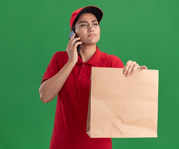Thinking looking at side young delivery girl wearing uniform and cap holding paper food package and speaks on phone isolated on green wall