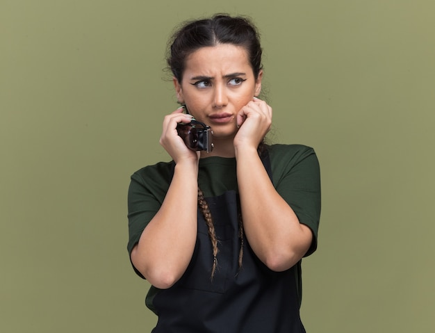Thinking looking at side young female barber in uniform holding hair clippers putting hands around face isolated on olive green wall