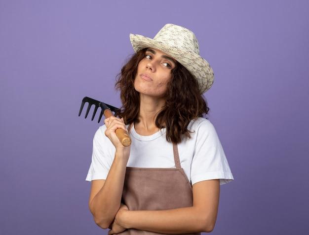 Pensando guardando al lato giovane giardiniere femminile in uniforme che indossa il cappello da giardinaggio tenendo il rastrello sulla spalla