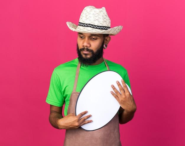 Pensando guardando lato giovane giardiniere ragazzo afroamericano che indossa cappello da giardinaggio tenendo fumetto isolato su parete rosa