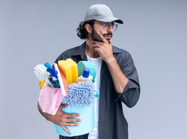 Pensando guardando al lato giovane bel ragazzo delle pulizie che indossa t-shirt e berretto che tiene secchio di strumenti di pulizia ha afferrato il mento isolato sul muro bianco