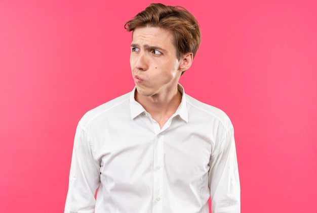 Thinking looking side young handsome guy wearing white shirt isolated on pink wall