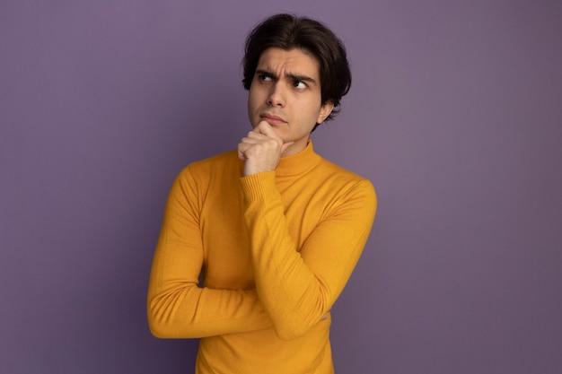 Pensando guardando al lato giovane bel ragazzo che indossa un maglione dolcevita giallo ha afferrato il mento isolato sulla parete viola con lo spazio della copia