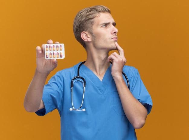 Pensando guardando al lato giovane medico maschio che indossa l'uniforme del medico con lo stetoscopio che tiene le pillole mettendo la mano sotto il mento isolato sulla parete arancione