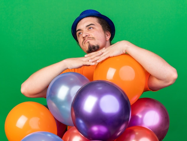 Thinking looking side young man wearing party hat standing behind balloons isolated on green wall