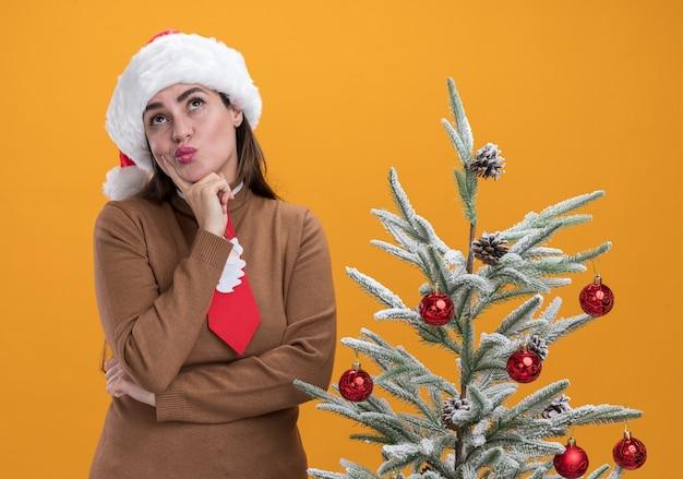Pensando guardando la giovane bella ragazza che indossa il cappello di natale con cravatta in piedi vicino albero di natale mettendo il dito sulla guancia isolato sul muro arancione