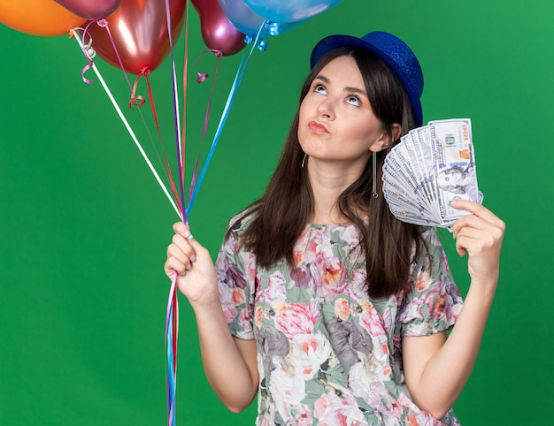Thinking looking up young beautiful girl wearing party hat holding balloons with cash isolated on green wall