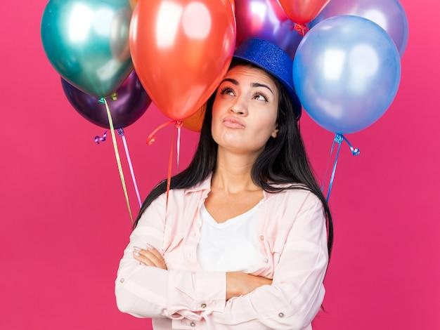 분홍색 벽에 격리된 손을 건너는 풍선 앞에 서 있는 파티 모자를 쓴 아름다운 젊은 여성을 올려다보는 생각