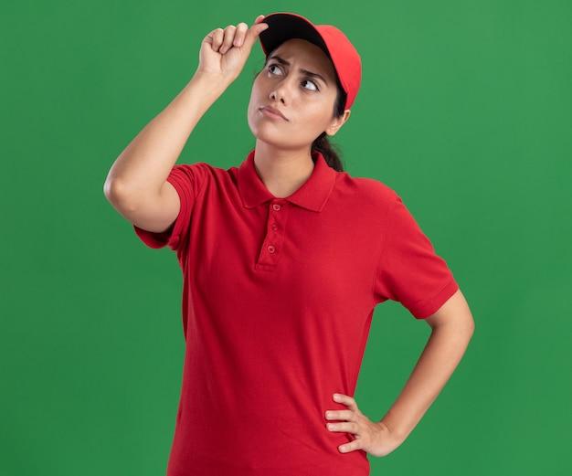 Pensando che osserva in su la giovane ragazza di consegna che indossa l'uniforme e la protezione della tenuta del cappuccio isolata sulla parete verde