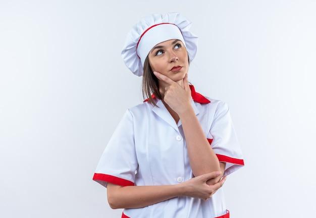 白い壁に隔離されたシェフの制服をつかんだあごを身に着けている若い女性料理人を見上げることを考えて