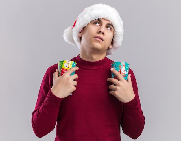 白い背景で隔離のクリスマスカップを保持しているクリスマス帽子をかぶって若い男を見上げることを考えて