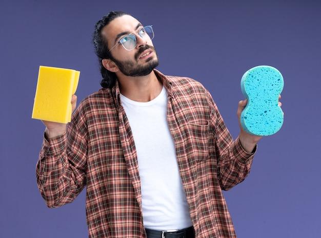 Думая, глядя вверх, молодой красивый уборщик в футболке с губками, изолированными на синей стене