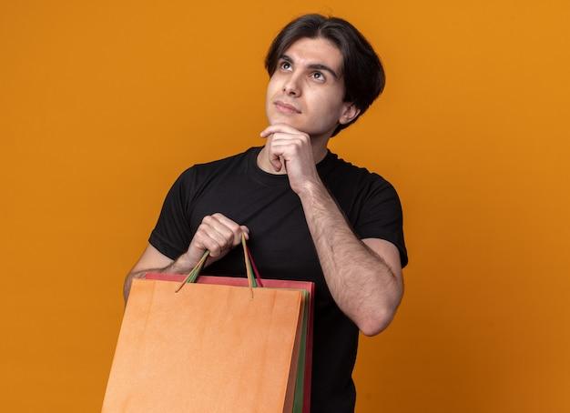 Pensando che osserva in su giovane ragazzo bello che porta la borsa nera della tenuta della maglietta che mette la mano sul mento isolata sulla parete arancio