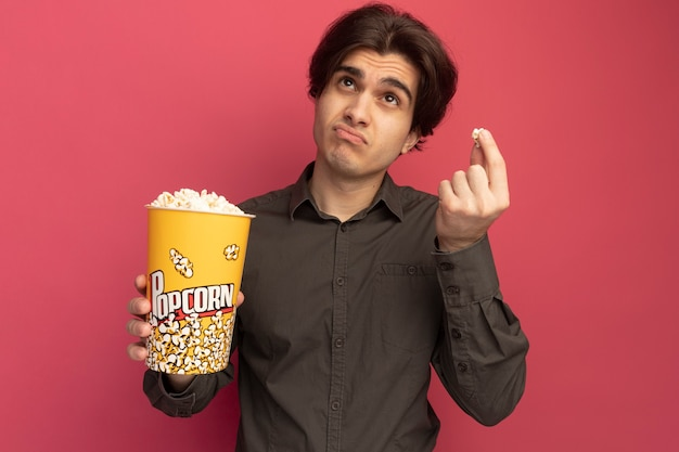 Pensando che osserva in su giovane ragazzo bello che porta la maglietta nera che tiene secchio di popcorn con pace popcorn isolato sulla parete rosa