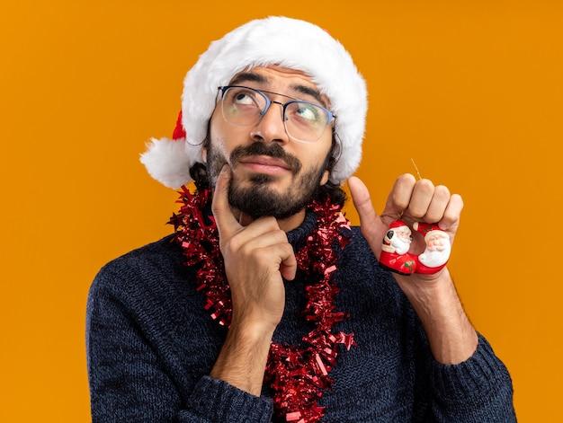 Pensando alla ricerca di giovane bel ragazzo che indossa il cappello di natale con la ghirlanda sul collo tenendo i giocattoli mettendo il dito sulla guancia isolato su sfondo arancione