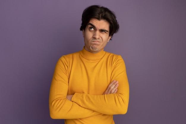 Pensando che osserva in su giovane bel ragazzo che indossa maglione dolcevita giallo che attraversa le mani isolate sulla parete viola