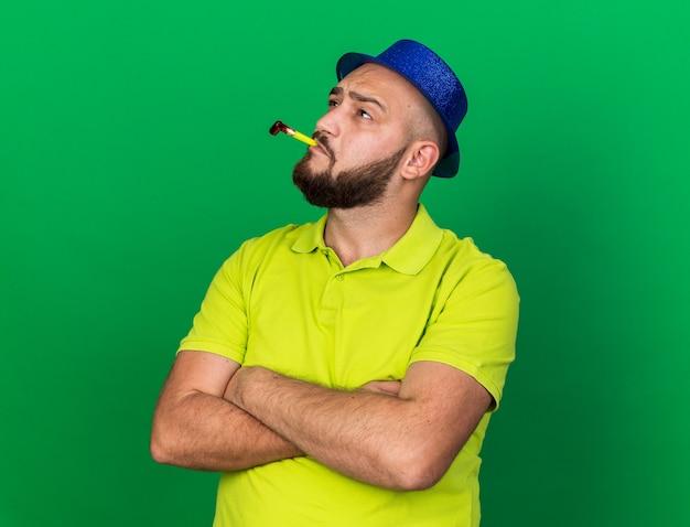 緑の壁に分離された手を交差するパーティー笛を吹く青いパーティーハットを身に着けている若い男を見上げることを考えて