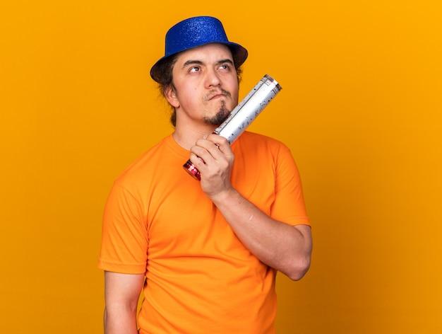 Думая, глядя вверх молодой человек в партийной шляпе держит пушку конфетти, изолированную на оранжевой стене