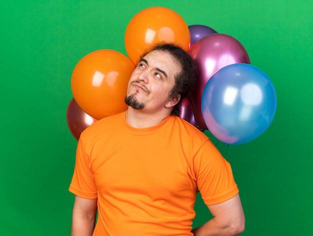 Thinking looking up young man wearing party hat standing in front balloons