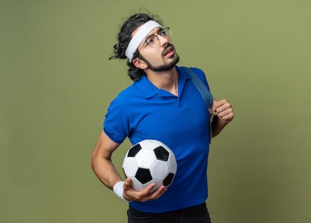 Думая, глядя вверх, молодой спортивный мужчина с повязкой на голову с браслетом и рюкзаком с мячом