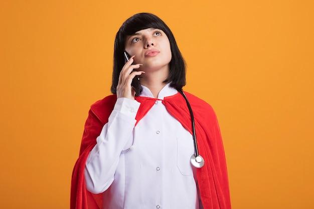 Думая, глядя вверх, молодая девушка-супергерой в стетоскопе с медицинским халатом и плащом разговаривает по телефону, изолированному на оранжевой стене
