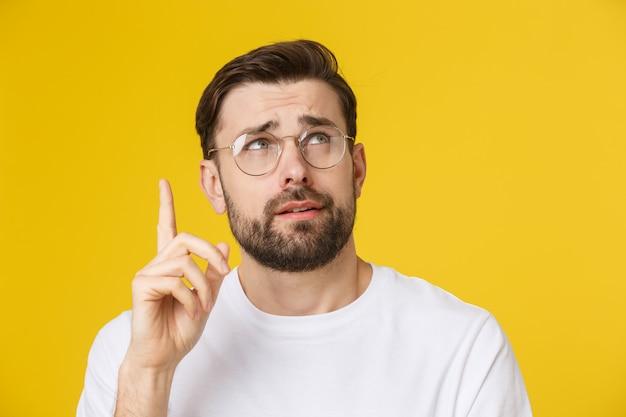 思考の男copyspaceを見上げてカジュアルな若い物思いにふける男のクローズアップの肖像画。白人男性モデル。